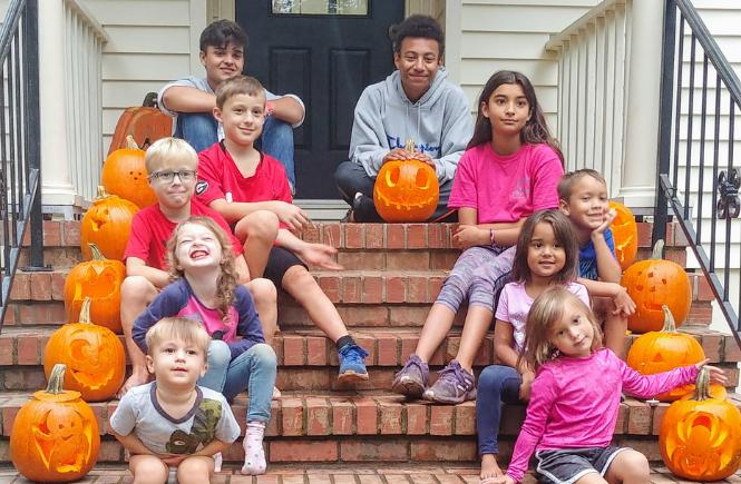front yard people, carving pumpkins